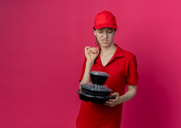 Annoyed young pretty delivery girl wearing red uniform and cap holding and looking at food containers isolated on crimson background with copy space