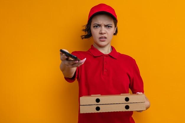 Infastidita giovane graziosa donna delle consegne che tiene in mano scatole per pizza e telefono