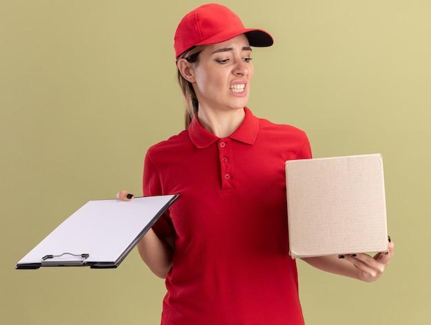 Раздраженная молодая красивая женщина-доставщик в униформе держит буфер обмена и смотрит на изолированную картонную коробку