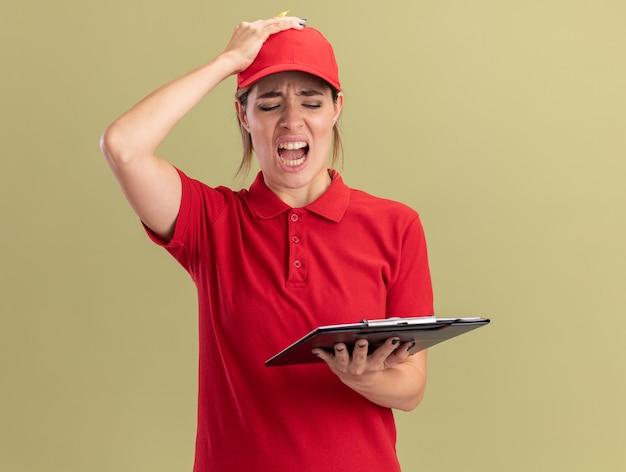 Раздраженная молодая красивая женщина-доставщик в униформе кладет руку на голову, держа карандаш, и смотрит в буфер обмена, изолированный на оливково-зеленой стене