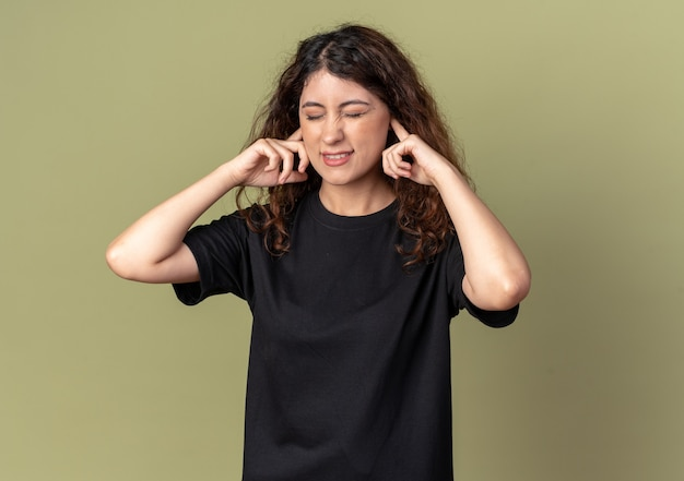 Annoyed young pretty girl putting fingers in ears with closed eyes