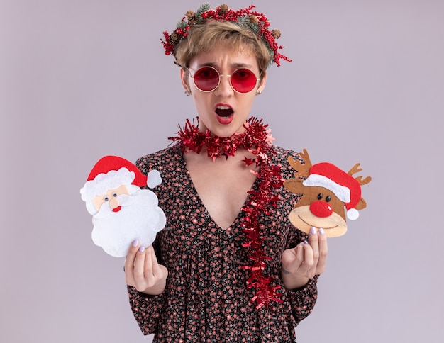 Annoyed young pretty girl wearing christmas head wreath and tinsel garland around neck with glasses holding christmas reindeer and santa claus paper ornaments  isolated on white wall
