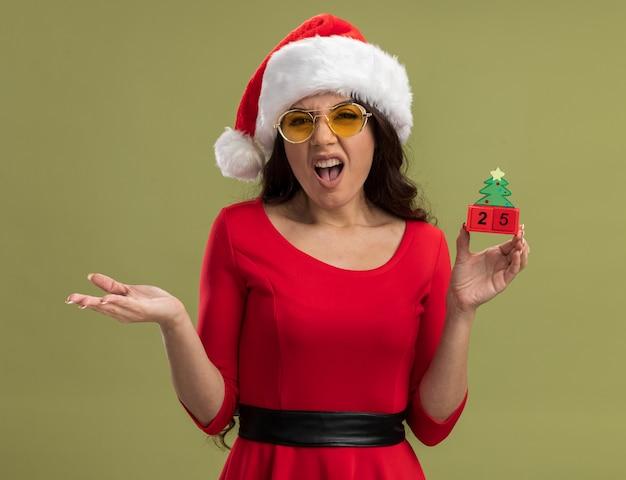 Раздраженная молодая красивая девушка в шляпе санта-клауса и очках держит елочную игрушку с датой, глядя, показывая пустую руку