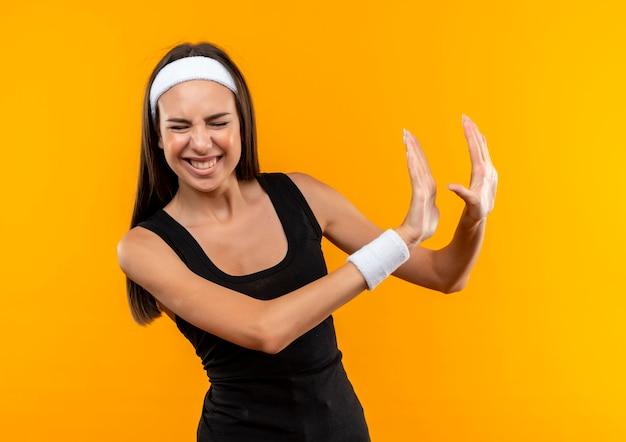 Раздраженная молодая симпатичная спортивная девушка с повязкой на голову и браслетом, жестом показывающая нет, с закрытыми глазами и вытянутыми руками, изолированными на оранжевой стене