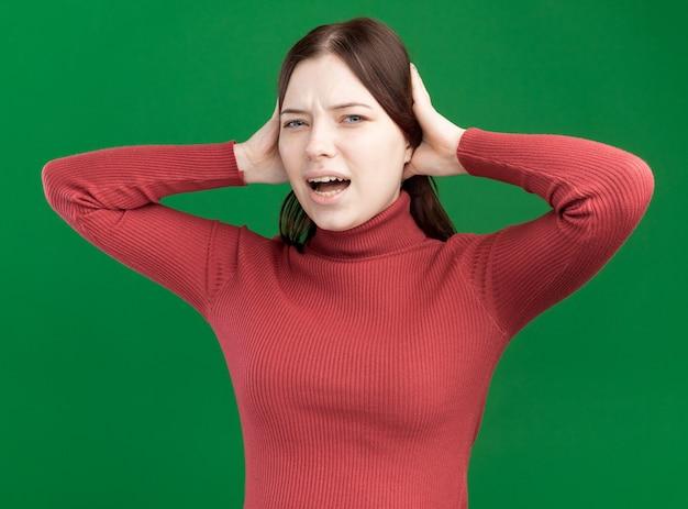 녹색 벽에 격리된 머리에 손을 얹고 앞을 바라보는 화난 젊은 예쁜 여자