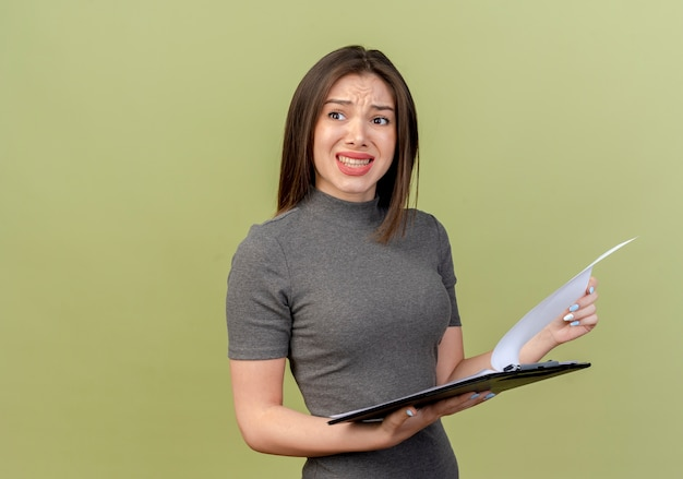 Infastidito giovane donna graziosa guardando a lato e tenendo appunti sulla parete verde oliva
