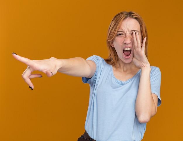 Ragazza giovane rossa irritata dello zenzero con le lentiggini che tengono la mano vicino alla bocca e che indica a lato sull'arancia