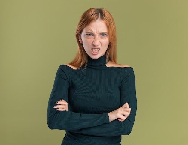 Infastidita giovane ragazza rossa allo zenzero con le lentiggini in piedi con le braccia incrociate isolate sulla parete verde oliva con spazio di copia