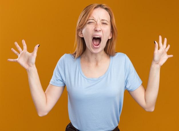 주근깨가 있는 어린 빨간 머리 생강 소녀는 복사 공간이 있는 주황색 벽에 고립되어 비명을 지르며 손을 들고 서 있다