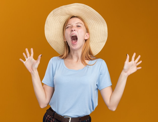 Annoyed young redhead ginger girl with freckles wearing beach hat standing with raised hands on orange
