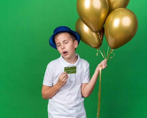 Раздраженный молодой славянский мальчик в синей партийной шляпе, держащий гелиевые шары и кредитную карту, изолированный на зеленой стене с копией пространства
