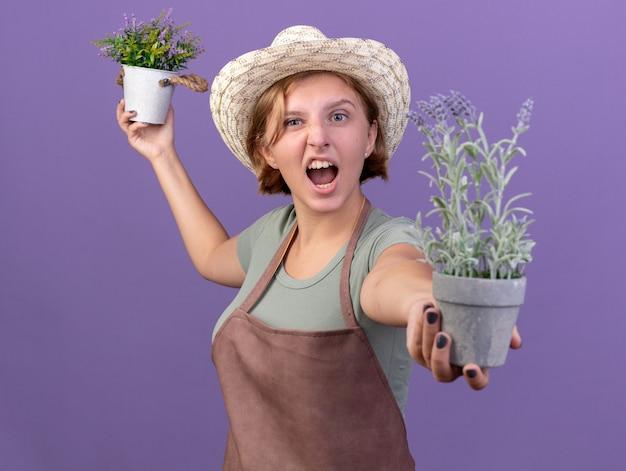 Infastidito giovane giardiniere femmina slava che indossa cappello da giardinaggio con fiori in vasi da fiori