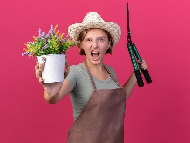 コピースペースとピンクの壁に分離された植木鉢でガーデニングはさみと花を保持しているガーデニング帽子をかぶってイライラする若いスラブ女性庭師