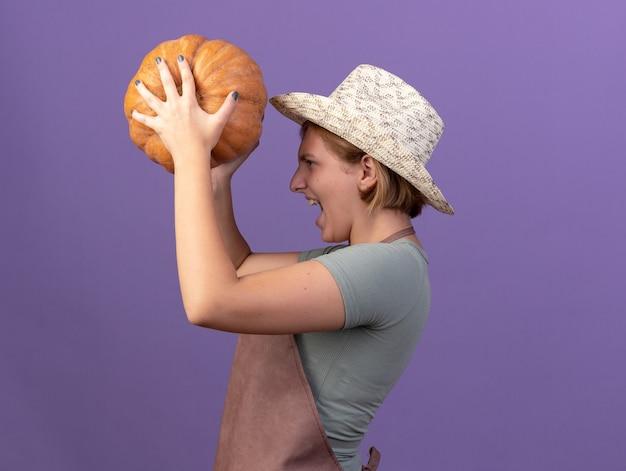 Il giovane giardiniere femminile slava infastidito che porta il cappello di giardinaggio sta lateralmente tenendo la zucca