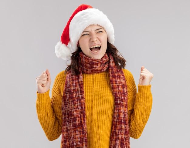 サンタの帽子と首にスカーフを持ったイライラした若いスラブの女の子は拳を保ち、コピースペースで白い壁に隔離された側を見ます