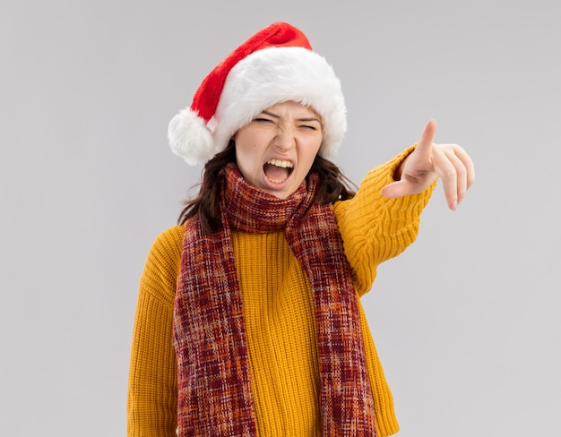 Annoyed young slavic girl with santa hat and with scarf around neck looking and pointing at side isolated on white wall with copy space
