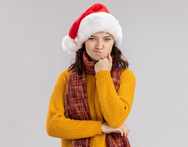Annoyed young slavic girl with santa hat and with scarf around neck puts hand on chin isolated on white wall with copy space