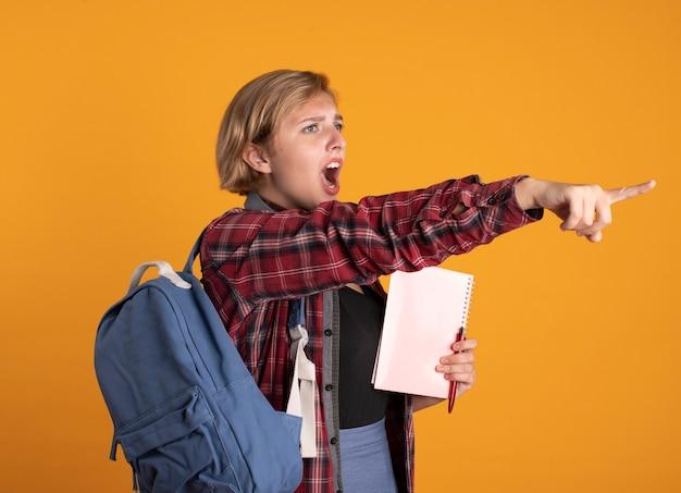 배낭을 착용하는 헤드폰으로 짜증이 난 젊은 슬라브 학생 소녀는 노트북과 펜을보고 측면을 가리키는 보유