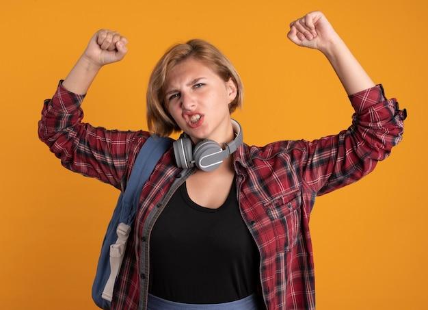 上げられた握りこぶしでバックパック スタンドを身に着けているヘッドフォンでイライラした若いスラブ学生の女の子
