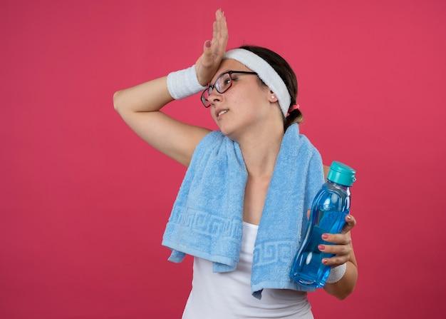 Раздраженная молодая спортивная девушка в оптических очках с полотенцем на шее, с повязкой на голову и браслетами держит бутылку с водой и кладет руку на лоб