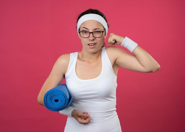 Una giovane ragazza sportiva infastidita con occhiali ottici che indossa fascia e braccialetti tende i bicipiti e tiene il tappetino sportivo