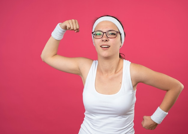 La giovane donna sportiva infastidita in occhiali ottici che indossa la fascia e i braccialetti tiene i pugni su e giù isolati sulla parete rosa