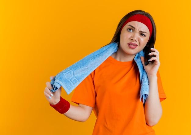 首にタオルをつかんでヘッドバンドとリストバンドを身に着けているイライラする若いスポーティな女性がまっすぐに見ている電話で話しているタオルをつかむ