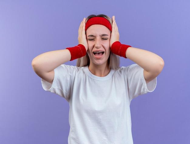 머리띠와 팔찌를 착용하는 중괄호와 짜증이 젊은 스포티 한 여자가 보라색 벽에 고립 된 귀에 손을 넣습니다.