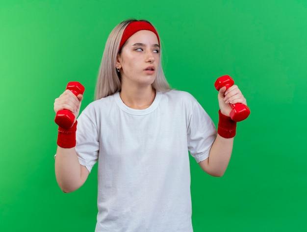 Infastidita giovane donna sportiva con le parentesi graffe che indossa fascia e braccialetti roteando gli occhi e tenendo i manubri isolati sulla parete verde