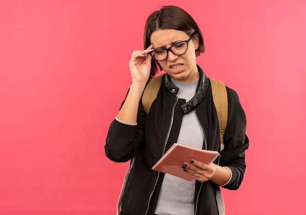Раздраженная молодая студентка в очках и задней сумке держит блокнот и очки с закрытыми глазами, изолированными на розовом с копией пространства