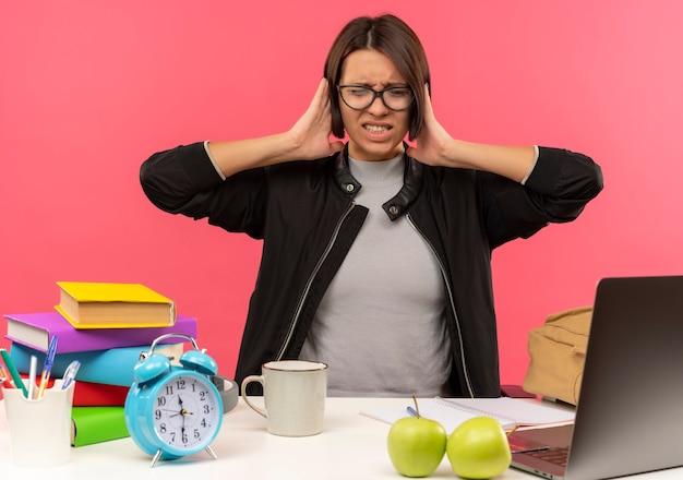 Ragazza giovane studente infastidita con gli occhiali seduto alla scrivania a fare i compiti mettendo le mani sulle orecchie con gli occhi chiusi isolati sul colore rosa