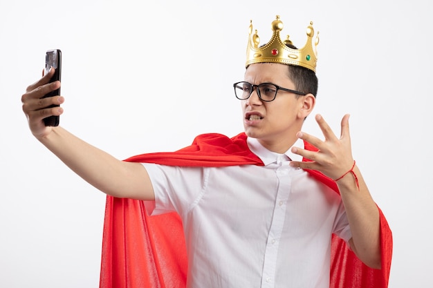Annoyed young superhero boy in red cape wearing glasses and crown keeping hand in air taking selfie isolated on white background