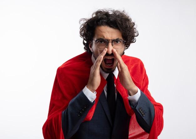 Раздраженный молодой супергерой в оптических очках в костюме с красным плащом держит руки близко ко рту и кричит на кого-то, смотрящего вперед, изолированного на белой стене