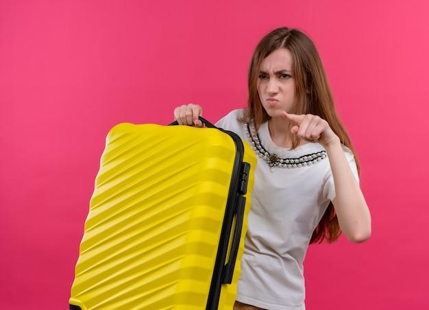 Раздраженная молодая девушка-путешественница держит чемодан и указывает на левую сторону на изолированном розовом пространстве