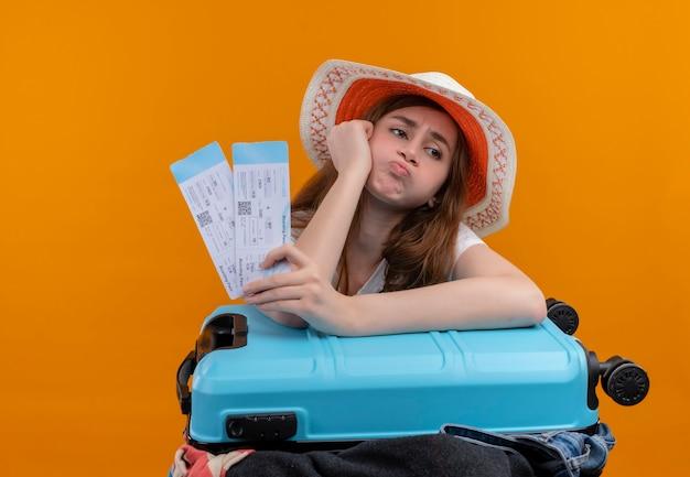 Раздраженная молодая путешественница в шляпе держит билеты на самолет и кладет руку на чемодан на изолированном оранжевом пространстве