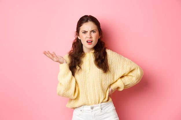Раздраженная молодая женщина жалуется на что-то странное, смущенно смотрит, поднимает руку с озадаченным лицом, стоит над розовой стеной.