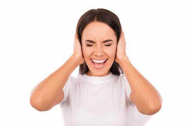 Раздраженная молодая женщина, закрывающая уши руками