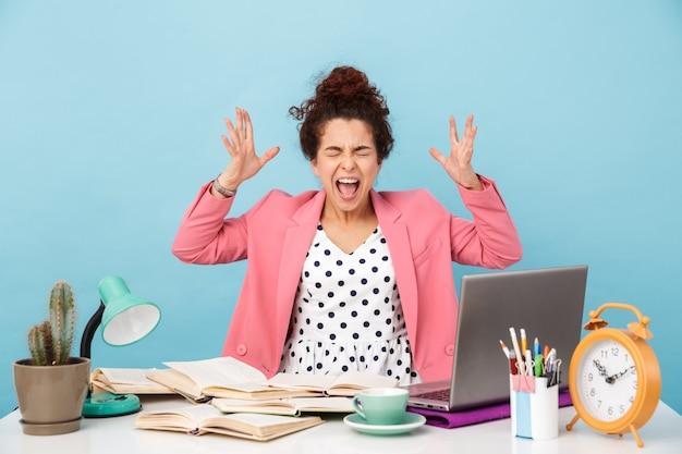 青い壁に隔離された机で作業中に叫んで手を投げてイライラする若い女性