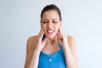 Annoyed young woman suffering from toothache and touching jaw.