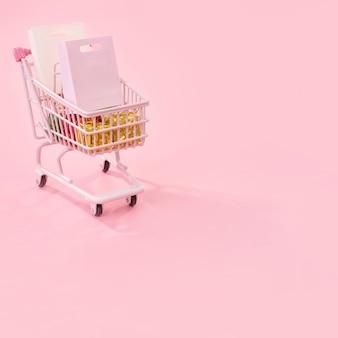 年間販売ショッピングシーズンのコンセプト-分離された紙袋ギフトでいっぱいのミニ赤いショップカートトロリー