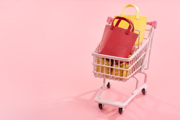 年間販売ショッピングシーズンのコンセプト-分離された紙袋でいっぱいのミニ赤いショップカートトロリー