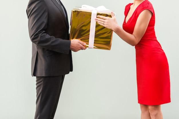 匿名のビジネスマンは赤いドレスを着た現在の女性を与えます。灰色の背景で撮影したスタジオ