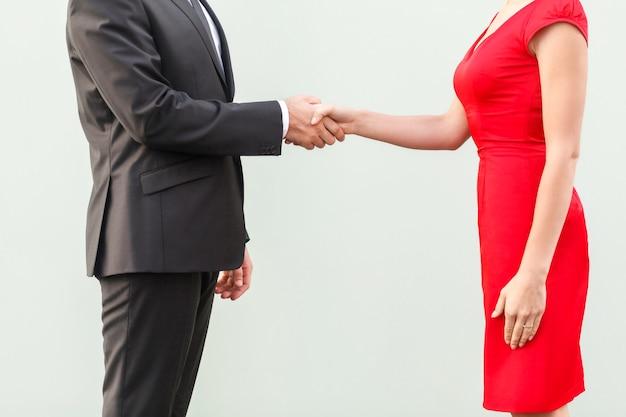 Анонимная сделка. рукопожатие, отмечаем сотрудничество. хорошо одетый деловой человек. студийный снимок, серый фон