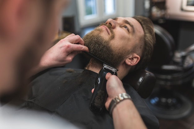 Anonymous barber trimming beard of man