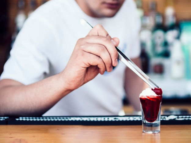 Anonymous bartender decorating red shot with cream and fruit