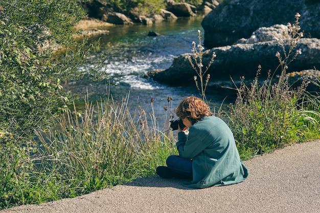 물 근처 해안에서 사진을 찍는 익명의 소년