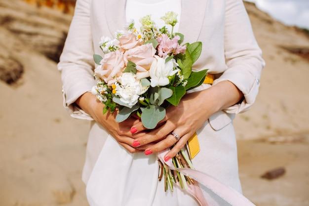 結婚式の花束を持つ匿名の花嫁が砂浜でクローズアップ。