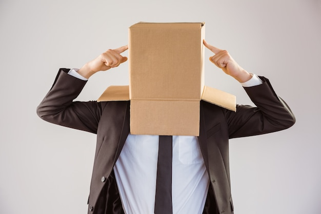 Anonymous businessman pointing to box on grey background