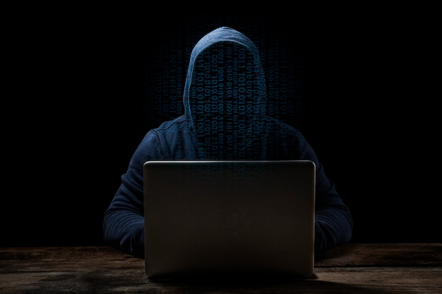 Anonymous computer hacker over abstract digital background. obscured dark face in mask and hood.