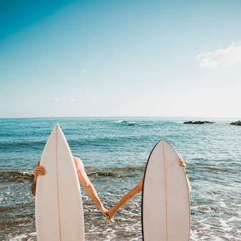 Anonymous couple behind surfboard holding hands